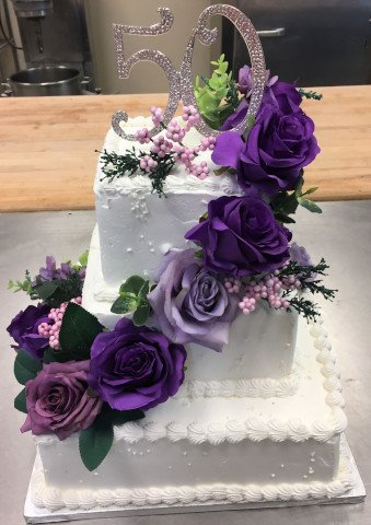 3 Tier cake with square layers and purple flowers for 50th anniversary