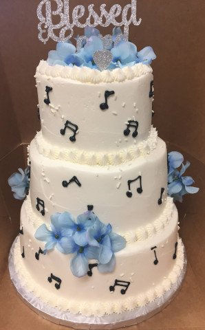 3 Tier Cake adorned with muscial notes on the layers and blue flowers for accent