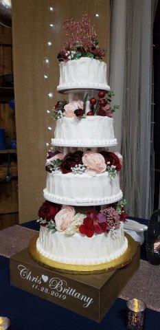 4 Tier Wedding cake with pillars and flowers between each tier