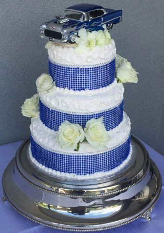 3 Tier Cake with roses and blue accents on each level and an antique car on top