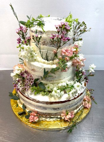 Naked tiered wedding cake dressed up with flowers